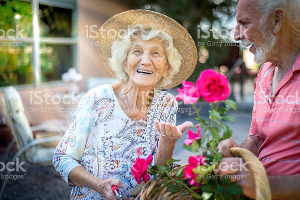 Old woman with flowers wearing hat