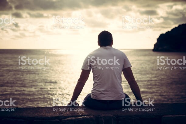 Sad man sitting on beach