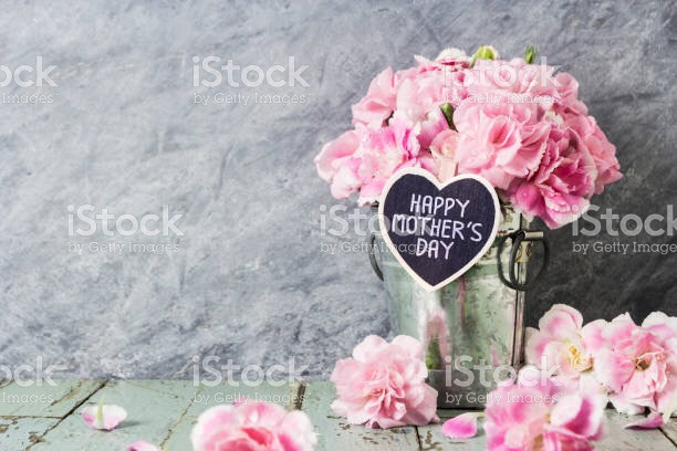 Bunch of glowers in glass vase with 'Happy Mother's Day' in heart - shaped card. Flowers surfound base